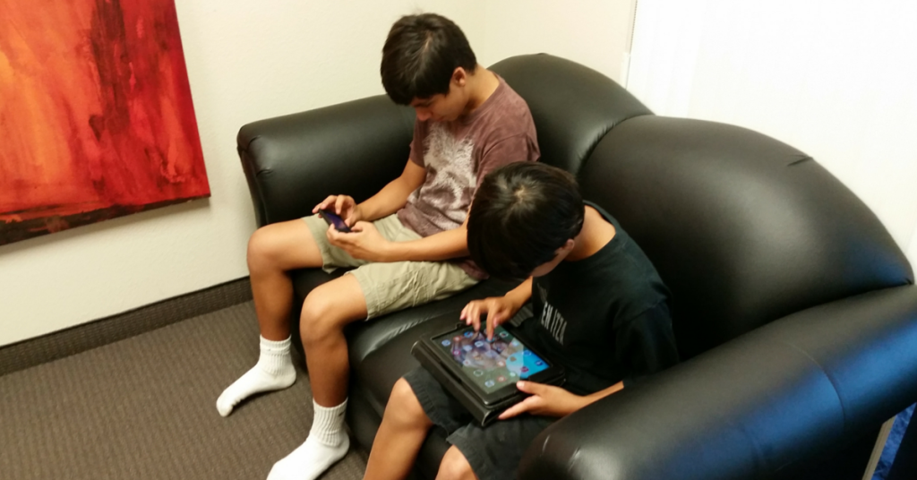 Image of two teenagers hunched over their phones